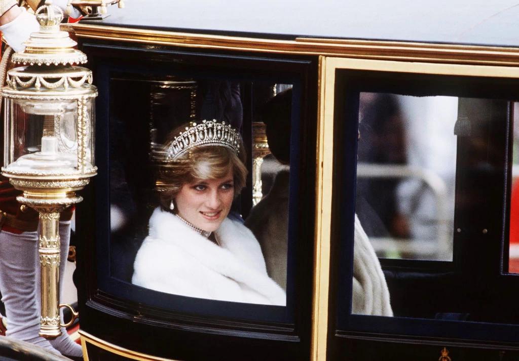 戴安娜王妃佩戴着剑桥情人结王冠、珍珠颈链和珍珠垂坠耳环出席议会开幕仪式